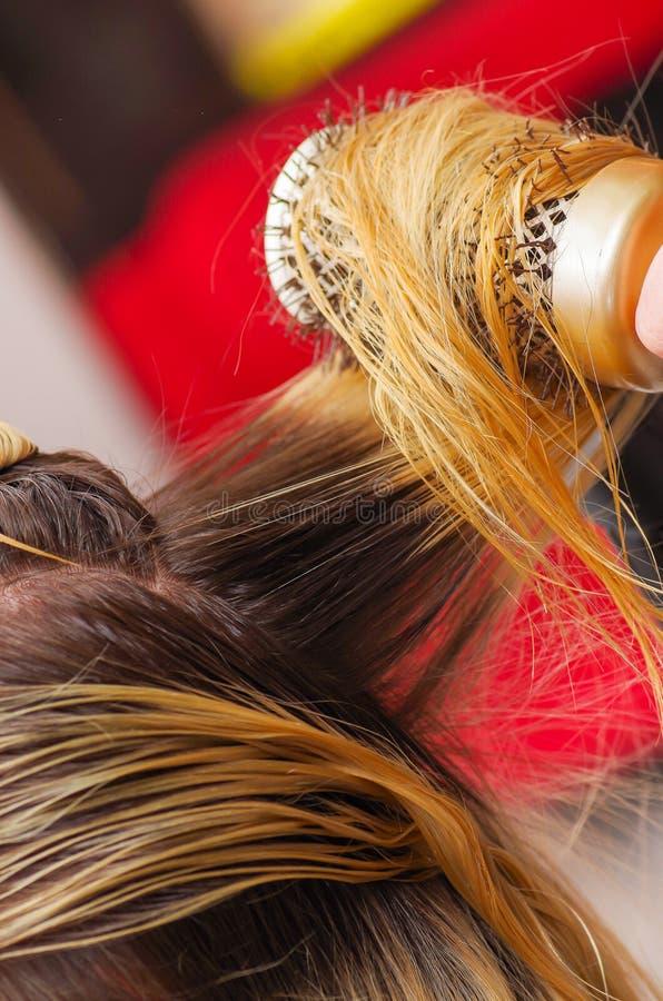 Zamyka up włosianego stylisty suszarniczy blondyn z włosianą suszarką i round muśnięciem w zamazanym tle obrazy royalty free