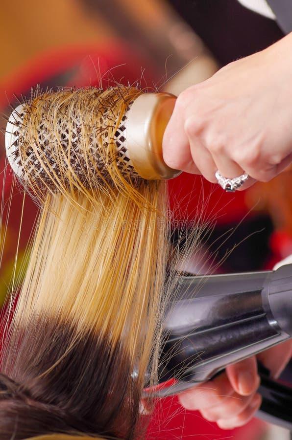 Zamyka up włosianego stylisty suszarniczy blondyn z włosianą suszarką i round muśnięciem w zamazanym tle obrazy stock