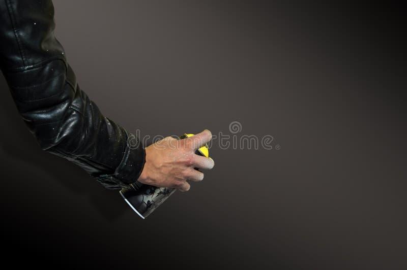 Zamyka up z młodą chłopiec robi graffiti, trzyma kiści puszkę z dwa rękami obraz stock