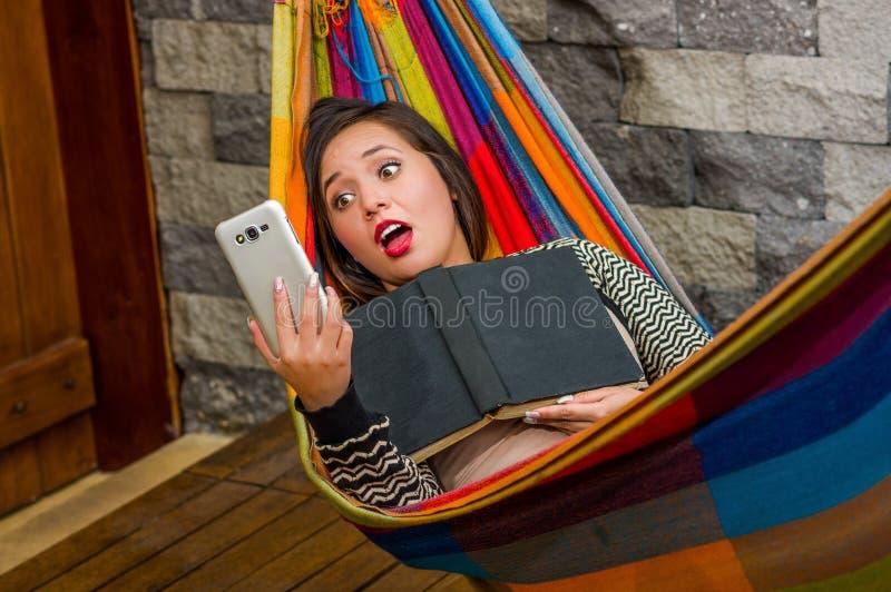 Zamyka up zdziwiona młoda piękna kobieta relaksuje w hamaku i bierze selfie z jej pastylką podczas gdy trzyma a obraz stock