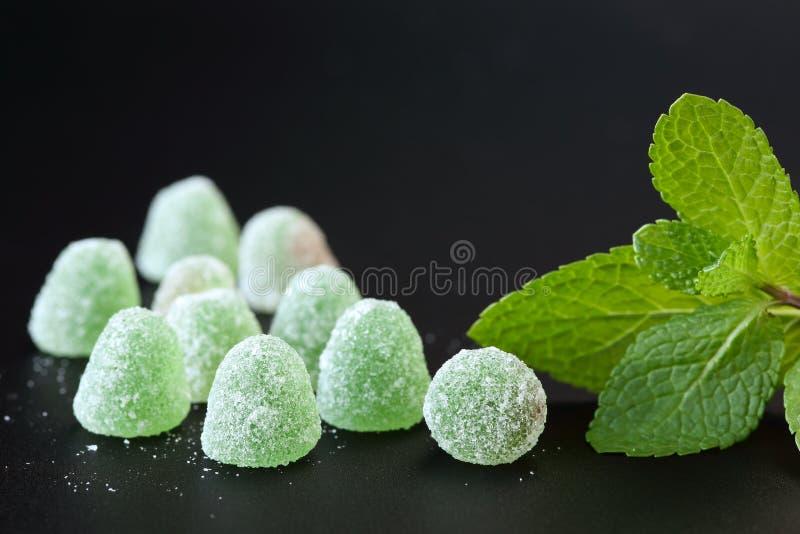 Zamyka up zieleń, nowej galarety krople z cukrowymi kryształami i spearmint liście na czarnym tle, zdjęcia royalty free