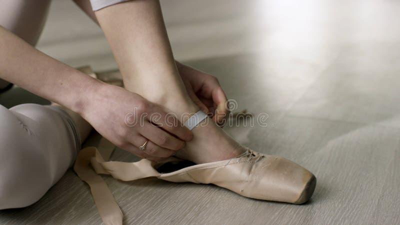 Zamyka w górę baletniczego tancerza kładzenia dla dalej, wiążący baletniczych buty Baleriny kładzenie na jej pointe kuje obsiadan obrazy stock