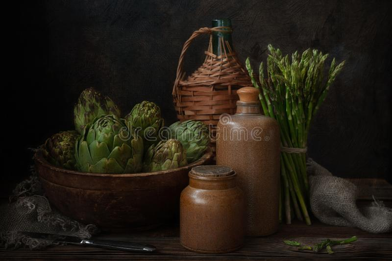Zamyka w górę fotografii świeży karczoch w starej drewnianej wiązce zielony asparagus i pucharze Wciąż życie na Ciemnym tle obraz royalty free