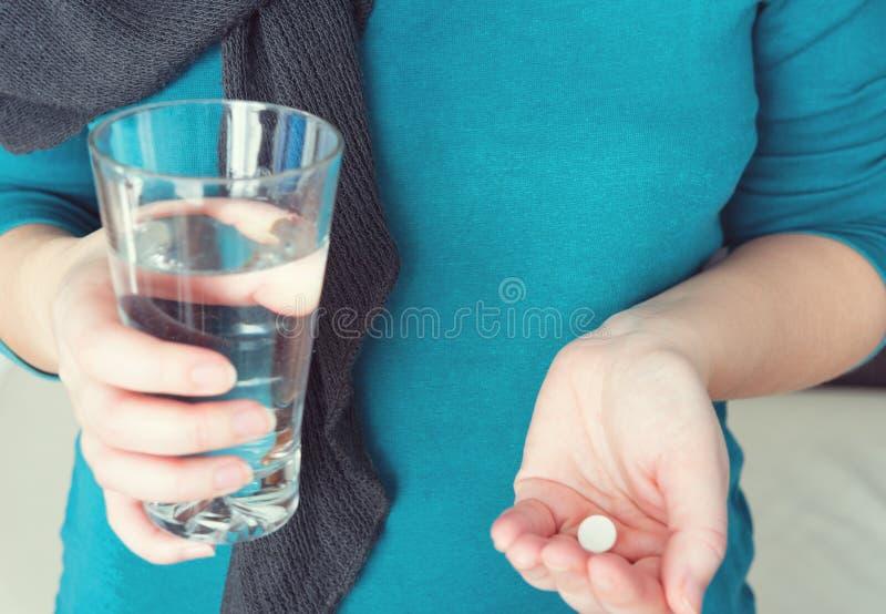 Zamyka w górę fotografii jeden round biała pigułka w młodej żeńskiej ręce Kobieta bierze medycyny z szkłem woda zdjęcia royalty free