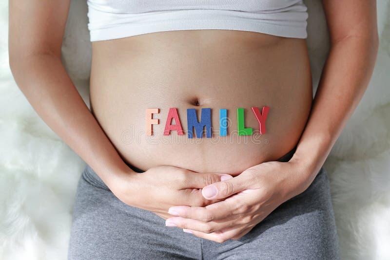 Zamyka w górę kobiety w ciąży obsiadania na miękkiej kanapie i macaniu jej brzuch z szyldową rodziną przed jej brzuchem zdjęcie royalty free