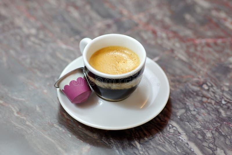 Zamyka w górę obrazka mała filiżanka i spodeczek, z kawową kawą espresso z tygrysa wzoru projektem na marmurowym tle, Biały i róż obrazy stock
