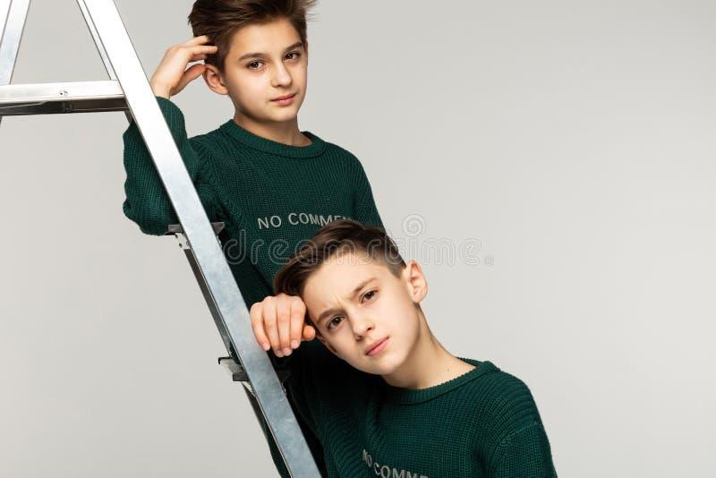 Zamyka w górę portreta braci nastolatkowie w zielonych pulowerach zdjęcie stock