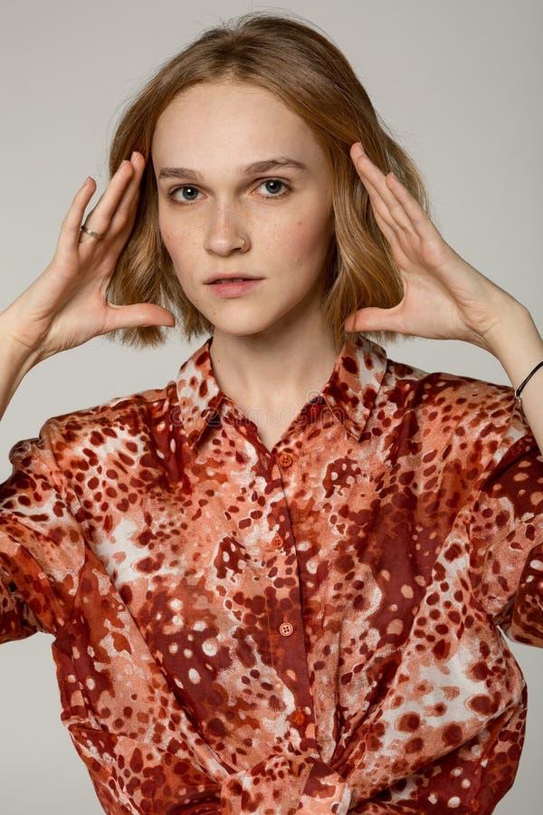 Zamyka w górę portreta piękna blondynki dziewczyna w czerwonej koszula z przebijaniem w nosie zdjęcie royalty free