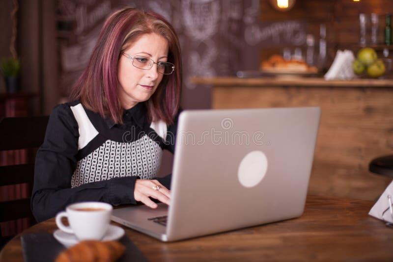 Zamyka w górę portreta pracuje na laptopie dorosły bizneswoman obrazy royalty free
