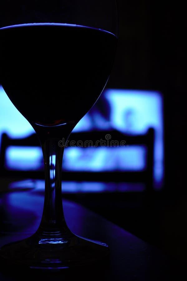 Zamyka w górę szkła wina obsiadanie na stole w zmroku, fotografia stock