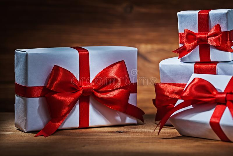 Zamyka w górę widoków białych giftboxes z czerwonymi faborkami fotografia stock