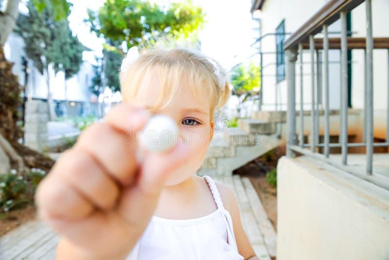Zamyka w górę ślicznej małej blondy berbeć dziewczyny w bielu smokingowym daje małym słodkim round cukierku dla ciebie Selekcyjna obraz royalty free