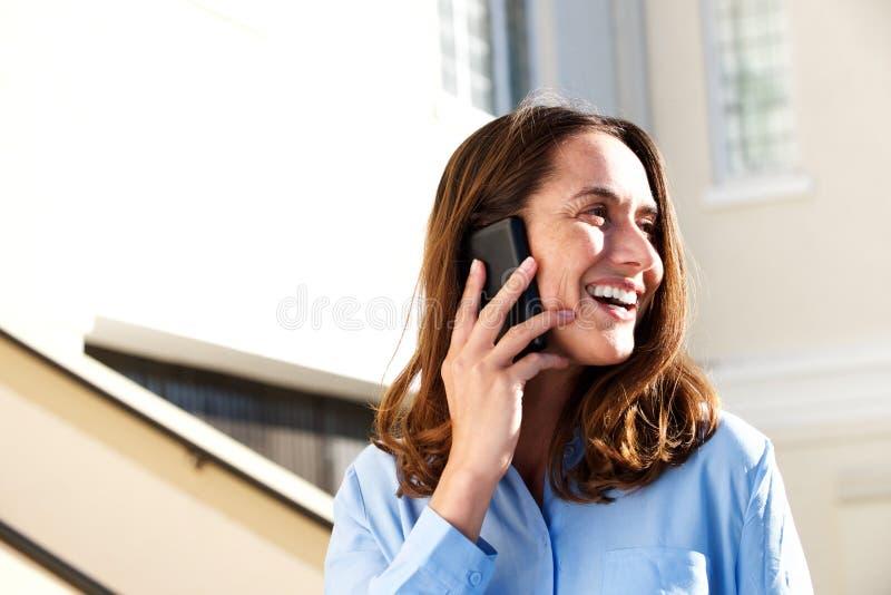 Zamyka w górę w średnim wieku kobiety ono uśmiecha się outdoors i opowiada na telefonie komórkowym obrazy royalty free