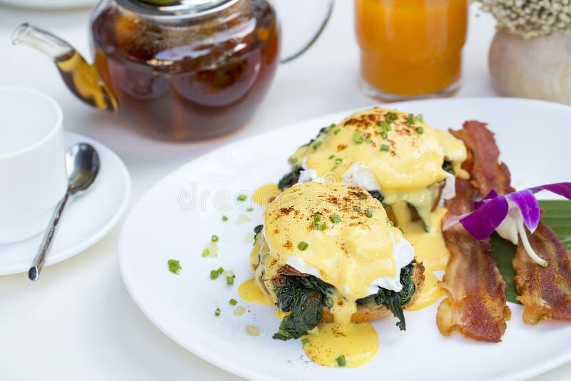Zamyka w górę świeżego jajecznego Benedykt śniadania z Czarną kawą i sokiem pomarańczowym obraz stock