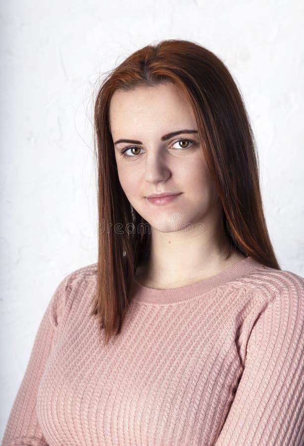 Zamyka w górę żeńskiego nastolatka z zdrową czystą świeżą skórą w różowym pulowerze, patrzejący kamerę Portret studencka dziewczy fotografia royalty free