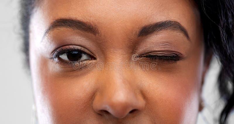 Zamyka w górę amerykanin afrykańskiego pochodzenia kobiety mruga jeden oko zdjęcia stock