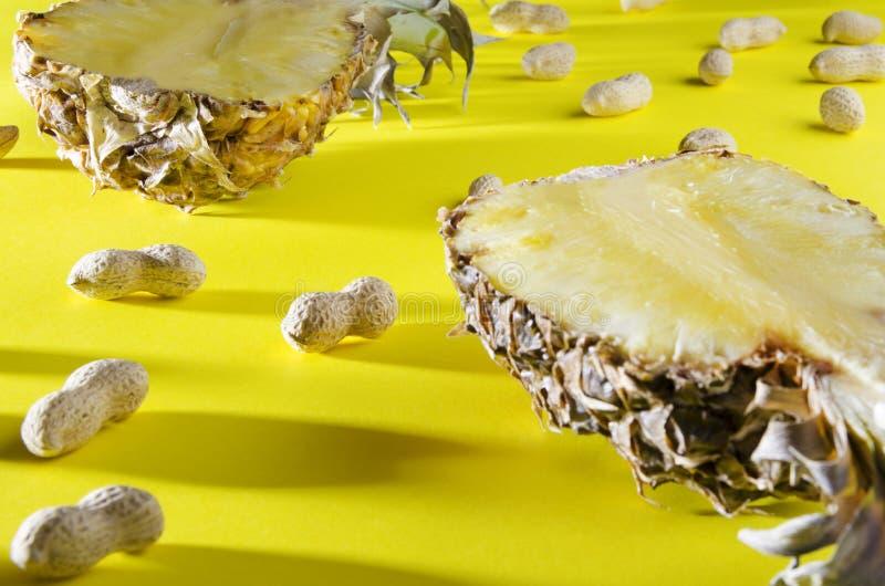 Zamyka w górę ananasa i arachidów w skorupie na kolorowym tle Strzelający z cieniem obrazy royalty free