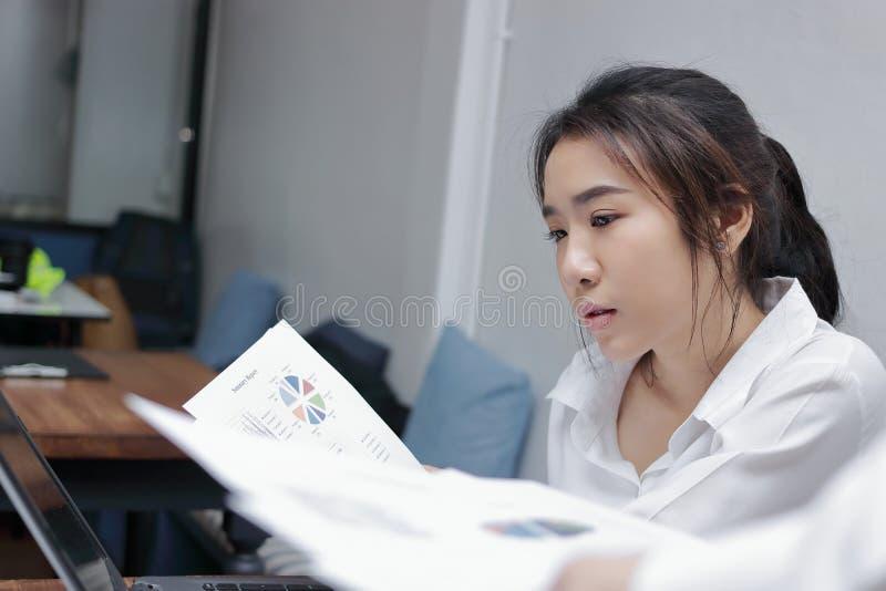 Zamyka w górę atrakcyjnej młodej Azjatyckiej biznesowej kobiety pracuje w biurze obrazy stock