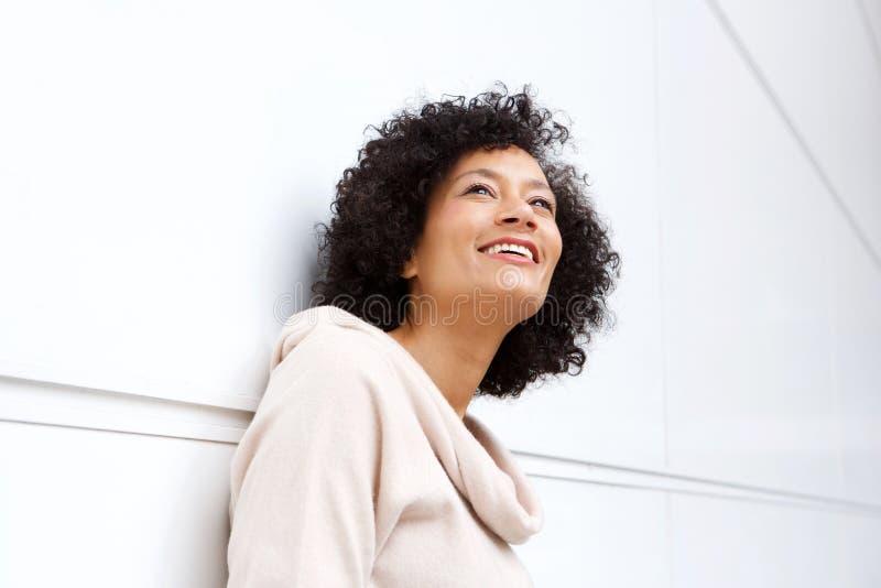 Zamyka w górę atrakcyjnej wieka średniego amerykanin afrykańskiego pochodzenia kobiety ono uśmiecha się w kontemplacji zdjęcia royalty free