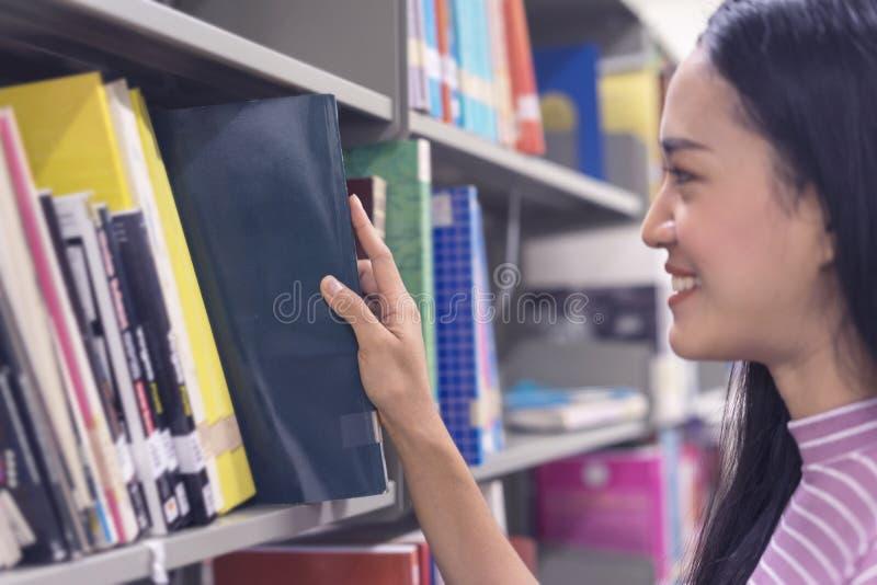 Zamyka w górę, Azjatycki student collegu wybiera książkę w bibliotece obrazy royalty free