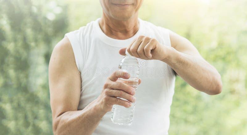 Zamyka w górę Azjatyckiej starszego mężczyzna mienia butelki woda zdjęcia royalty free