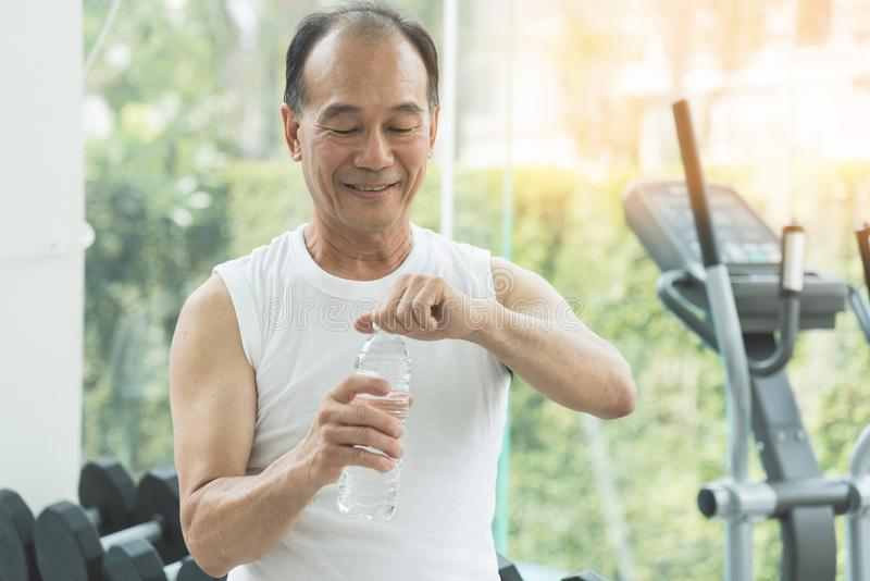 Zamyka w górę Azjatyckiej starszego mężczyzna mienia butelki woda fotografia royalty free
