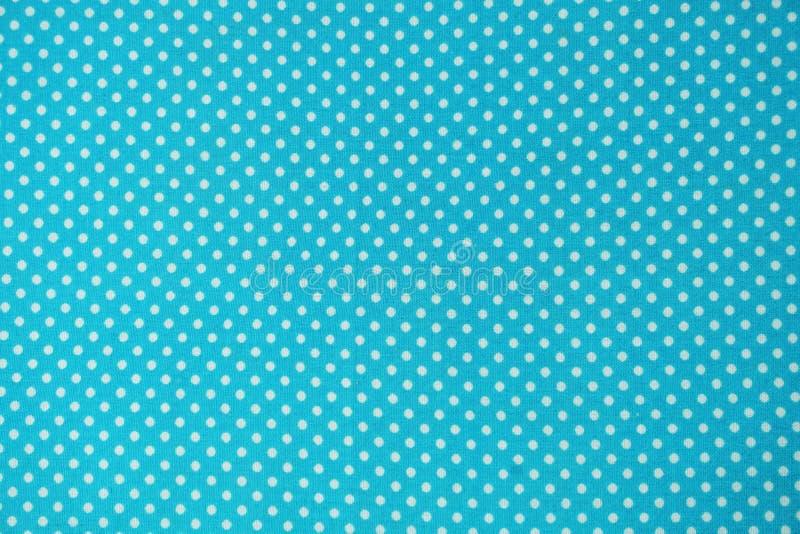 Zamyka w górę błękitnej tkaniny z białym polki kropki wzorem ilustracji