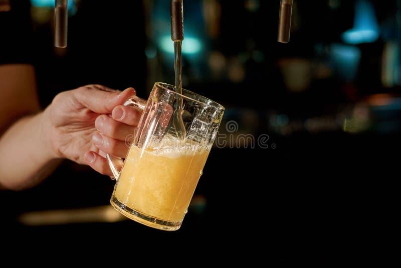 Zamyka w górę barman ręki dolewania piwa fotografia stock