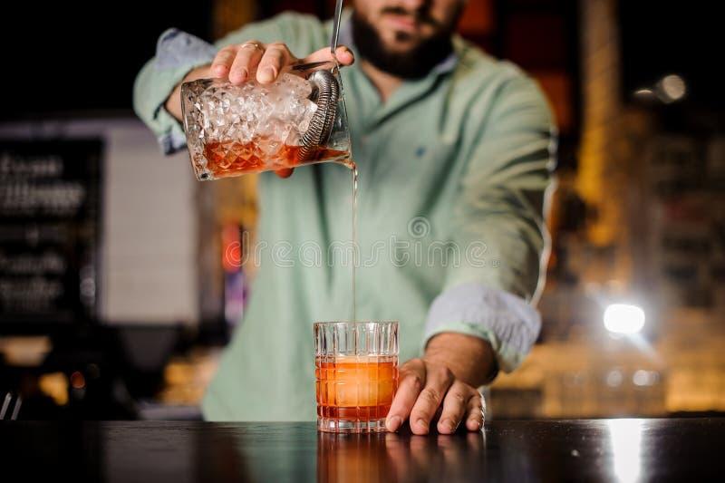 Zamyka w górę barmanu dolewania koktajlu w galanteryjnego szkło zdjęcie royalty free
