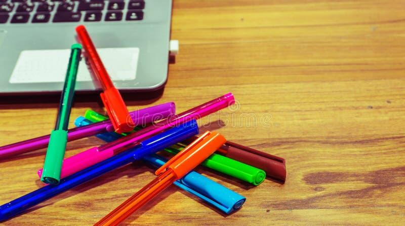 Zamyka w górę bealtiful pióro koloru labtop na stołowym biurze obrazy stock