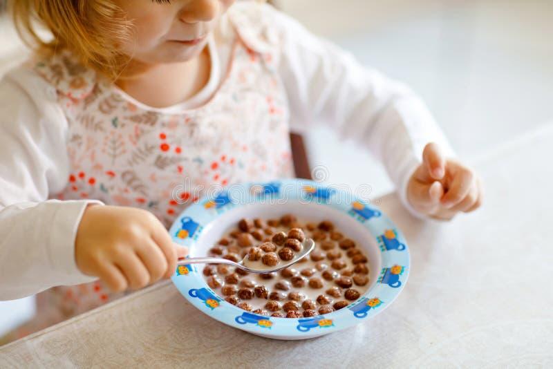 Zamyka w górę berbeć dziewczyny je zdrowego zboża z mlekiem dla śniadaniowego Ślicznego szczęśliwego dziecka dziecka w kolorowych zdjęcia royalty free
