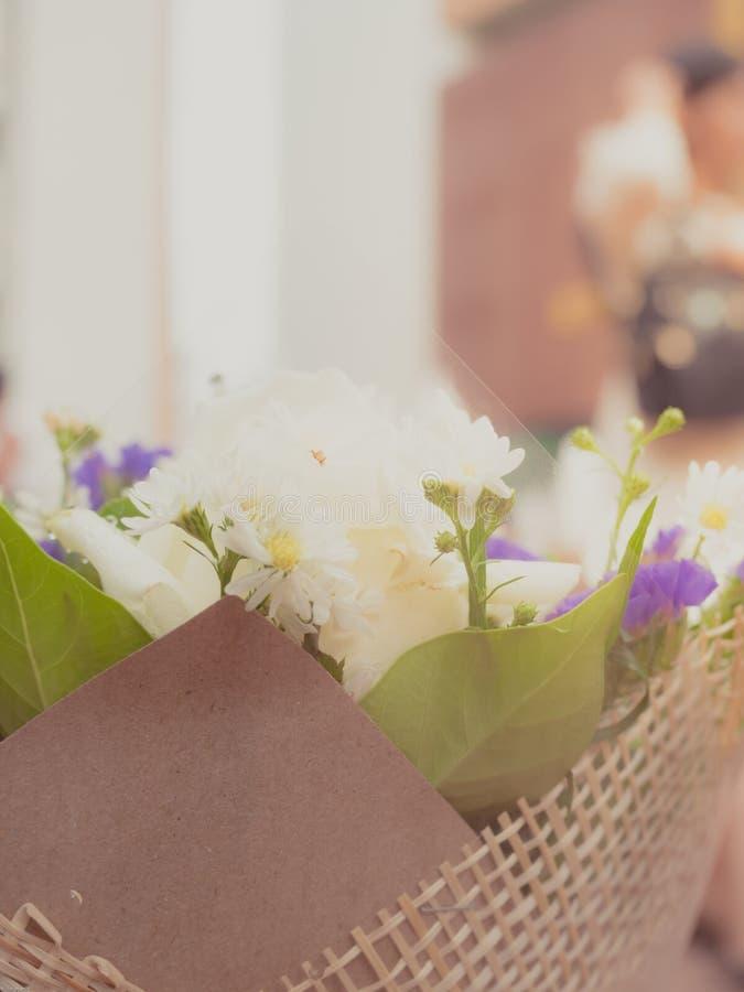 Zamyka w górę białego kwiatu i zielenieje liść paczkę w brown bukiecie z zdjęcie stock