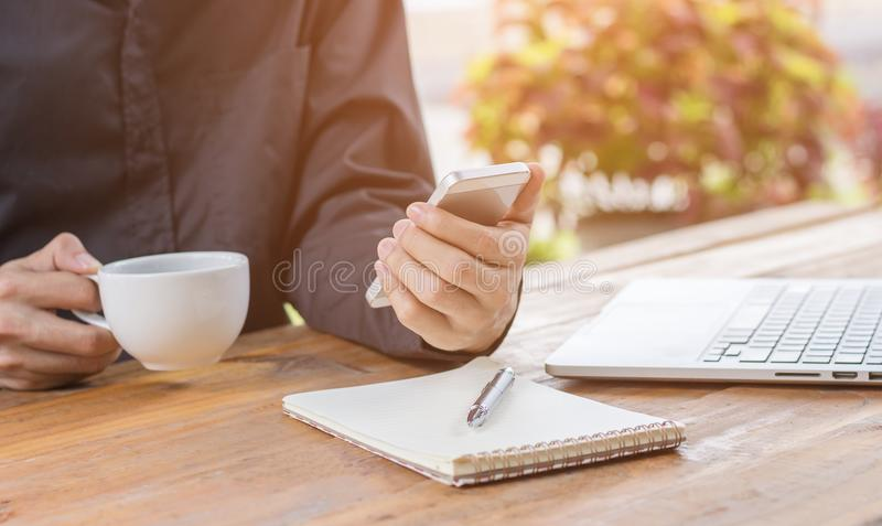Zamyka w górę biznesmena używać telefon komórkowego i trzymający filiżankę obraz royalty free