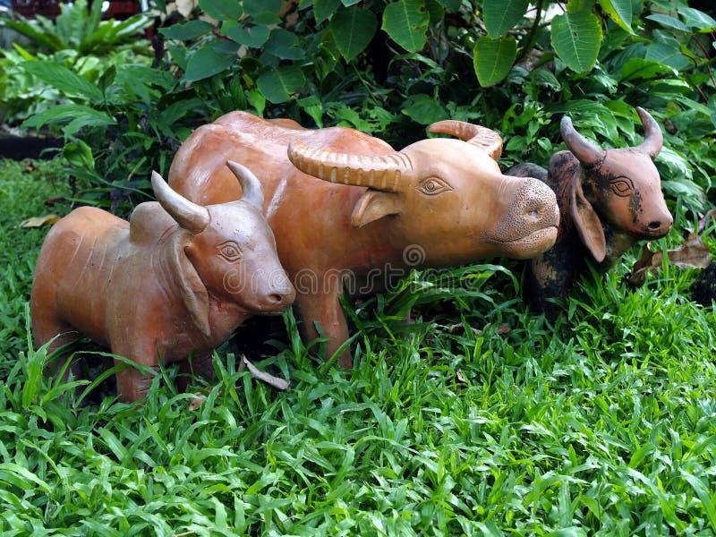 Zamyka w górę bizonu i krowa piec glinianej lali pozycji na zielonej trawy polu wśród świeżość bujny krzaka fotografia stock