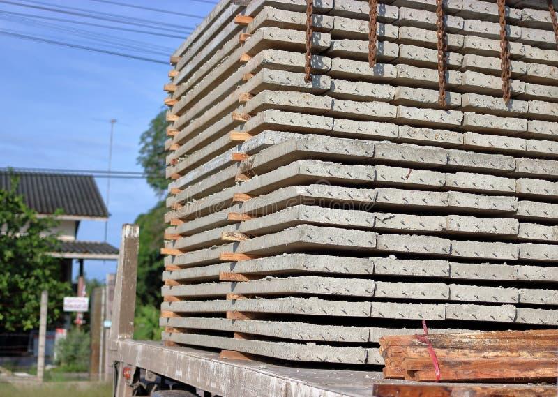 Zamyka w górę bocznego widoku ciężarówka broguje prestressed betonowe płyty dla budowy podczas gdy obciążeniowy obraz stock