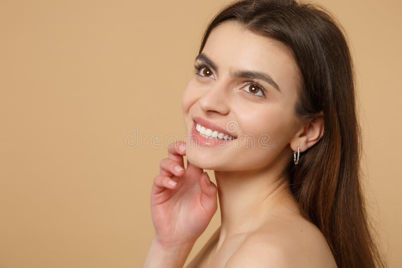 Zamyka w górę brunetki przyrodniej nagiej kobiety 20s z doskonalić skórą, naga postać uzupełnia odosobniony na beżowym pastel ści obrazy royalty free