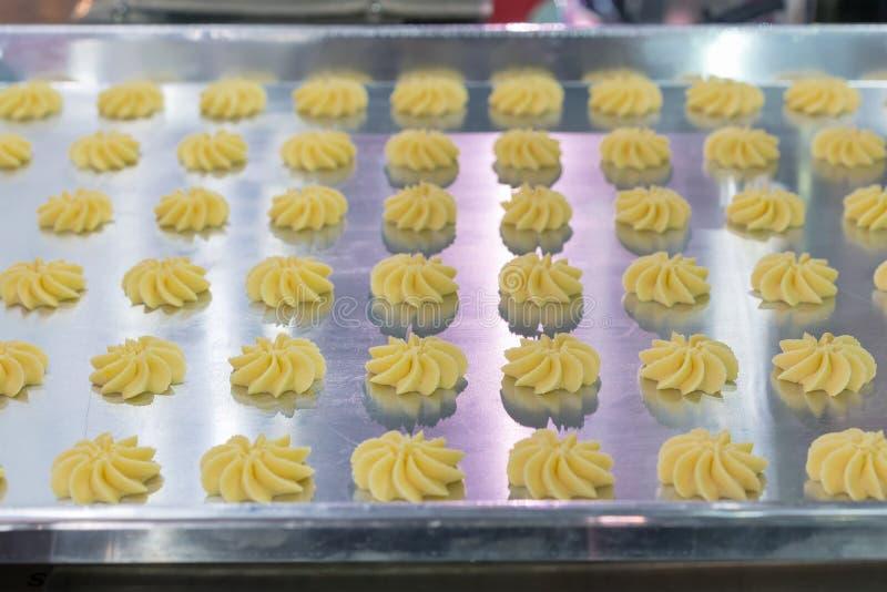 Zamyka w górę ciasta lub śmietanki na tacy automatyczny ciastko lub cukierki robi maszynie w linii produkcyjnej dla nowoczesna te zdjęcie stock