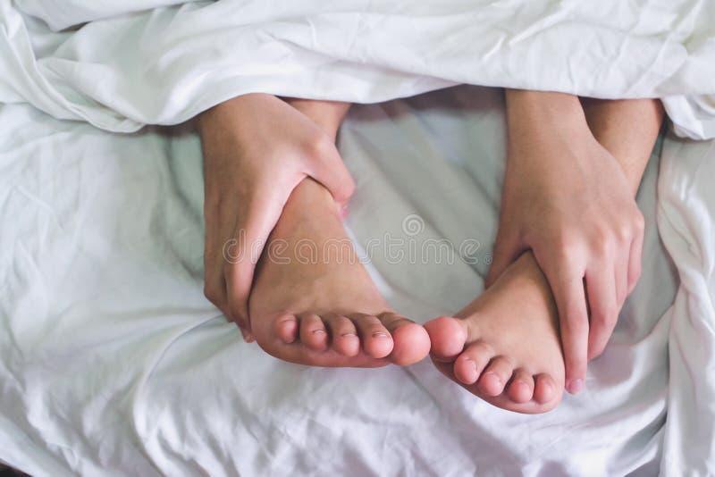 Zamyka w górę cieków na łóżku, dobiera się mieć płeć i zdjęcie stock