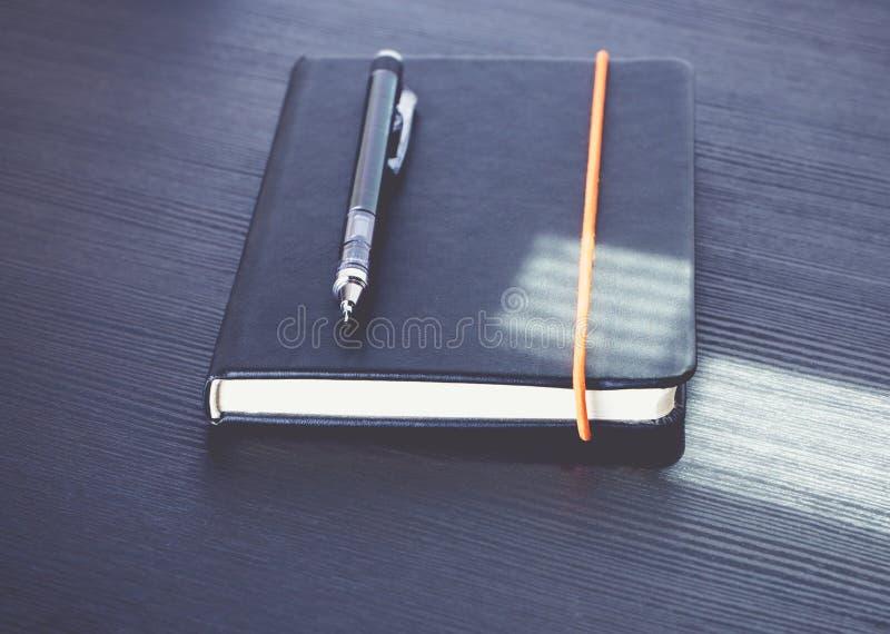 Zamyka w górę czarnego notatnika z nowożytnym machinalnym ołówkiem na czarnym w fotografia royalty free