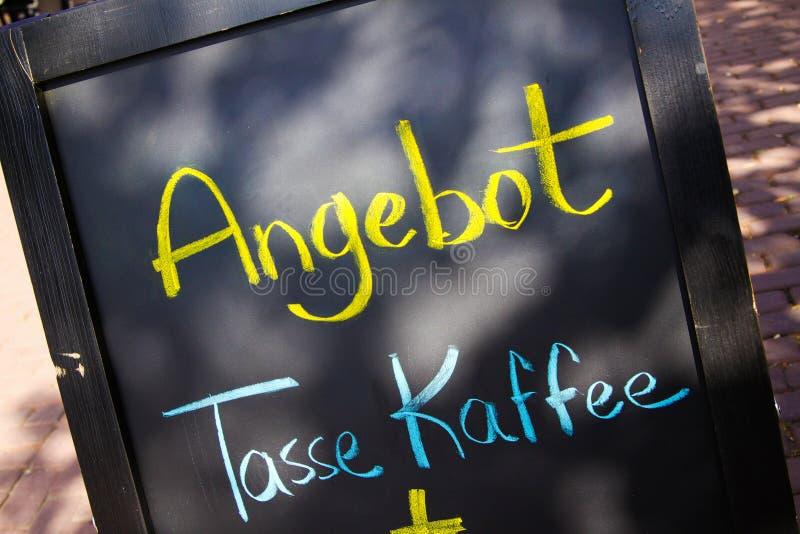 Zamyka w górę czarnej kredowej deski z żółtym i błękitnym ręcznie pisany wiadomość teksta znaczeniem: Oferuje filiżanka kawy zdjęcie stock