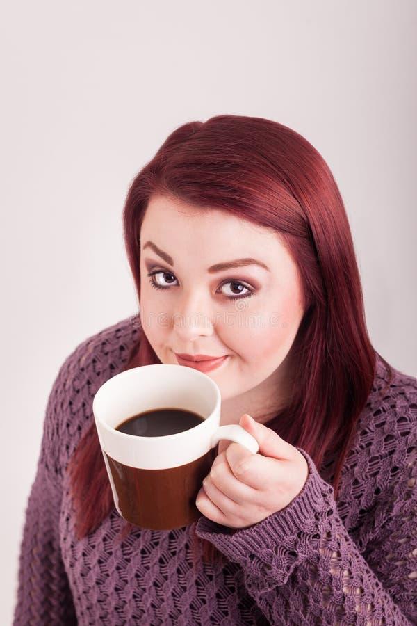 Zamyka w górę czerwieni głowy sączyć żeńskiej filiżanki ciepła kawa obraz stock