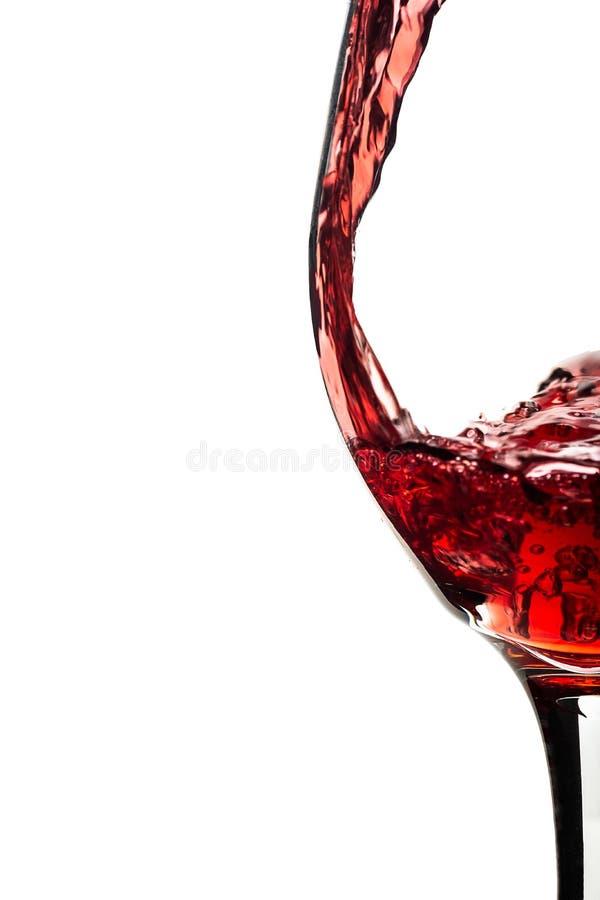 Zamyka w górę czerwonego wina nalewa w wina szkło na białych półdupkach obrazy stock
