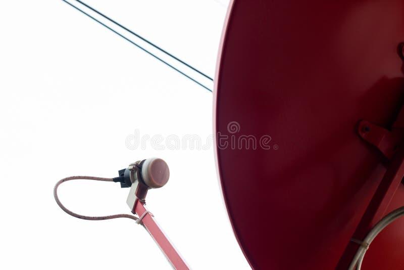 Zamyka w górę czerwonej anteny satelitarnej i tv anteny, przypowieściowy cyfrowy odbiorca dla komunikacyjnych dane na dachu z jas fotografia stock