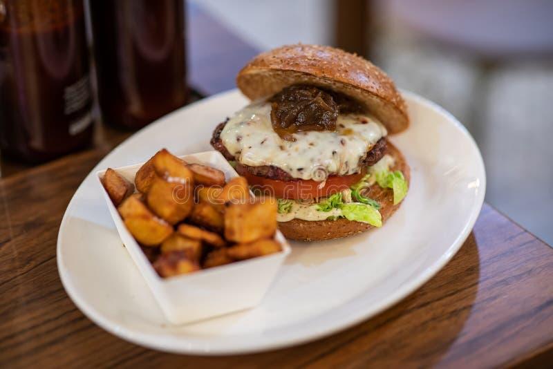Zamyka w górę domowej roboty hamburgeru z korzennymi grulami zdjęcie stock