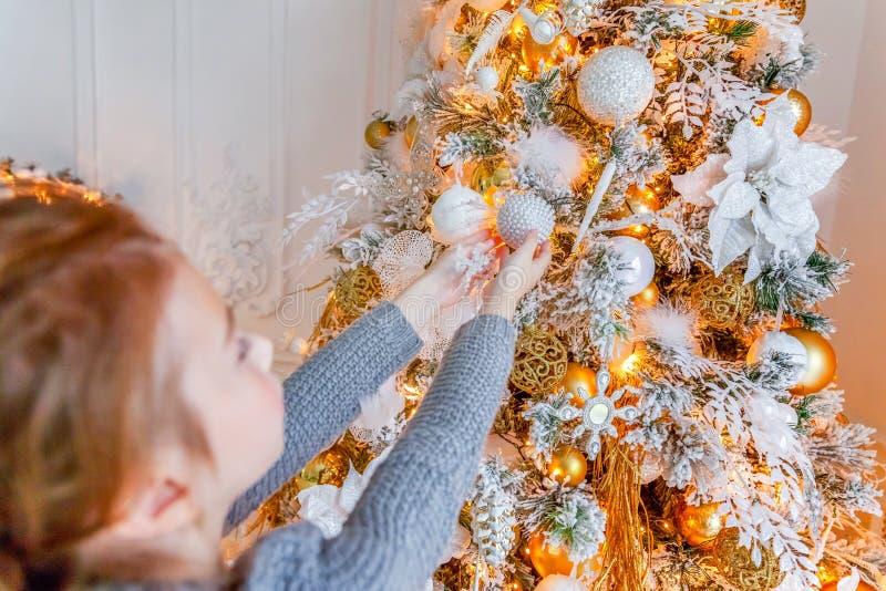 Zamyka w górę dziewczyn ręk dekoruje choinki w domu obraz stock