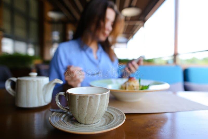 Zamyka w górę filiżanki herbata, czajnik i śliczny kobiety łasowania deser w zamazanym tle, przy kawiarnią, używać smartphone obraz royalty free