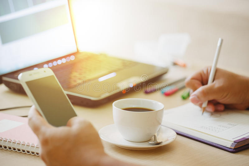 Zamyka w górę filiżanki kawy i laptopu z ręką biznesowy mężczyzna używa mądrze telefon zdjęcie stock