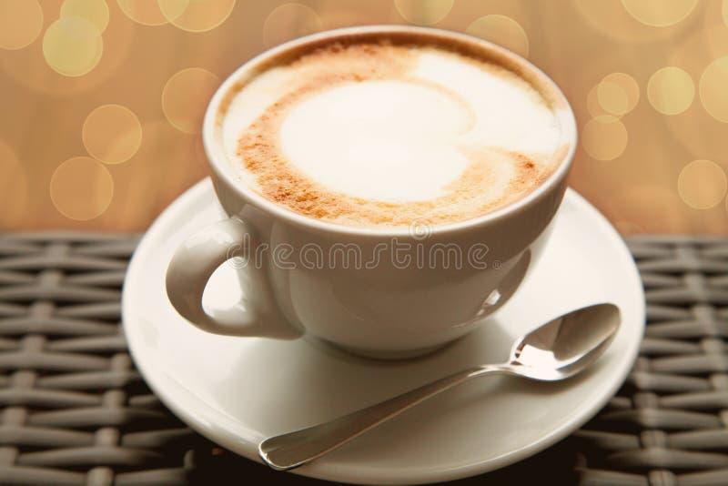Zamyka w górę filiżanki ofcapuccino latte sztuki kierowej kawy na drewnianym backgrou obraz royalty free