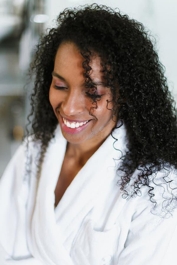 Zamyka w górę fotografii dosyć afro amerykańska dziewczyny pozycja w łazience i być ubranym białego bathrobe obraz stock