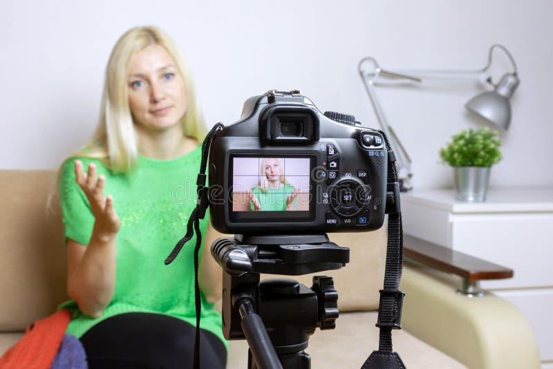 Zamyka w górę fotografii kamera na tripod z młodą womanon LCD plecy parawanową i zamazaną sceną na tle Żeński wideo blogger rejes zdjęcia royalty free